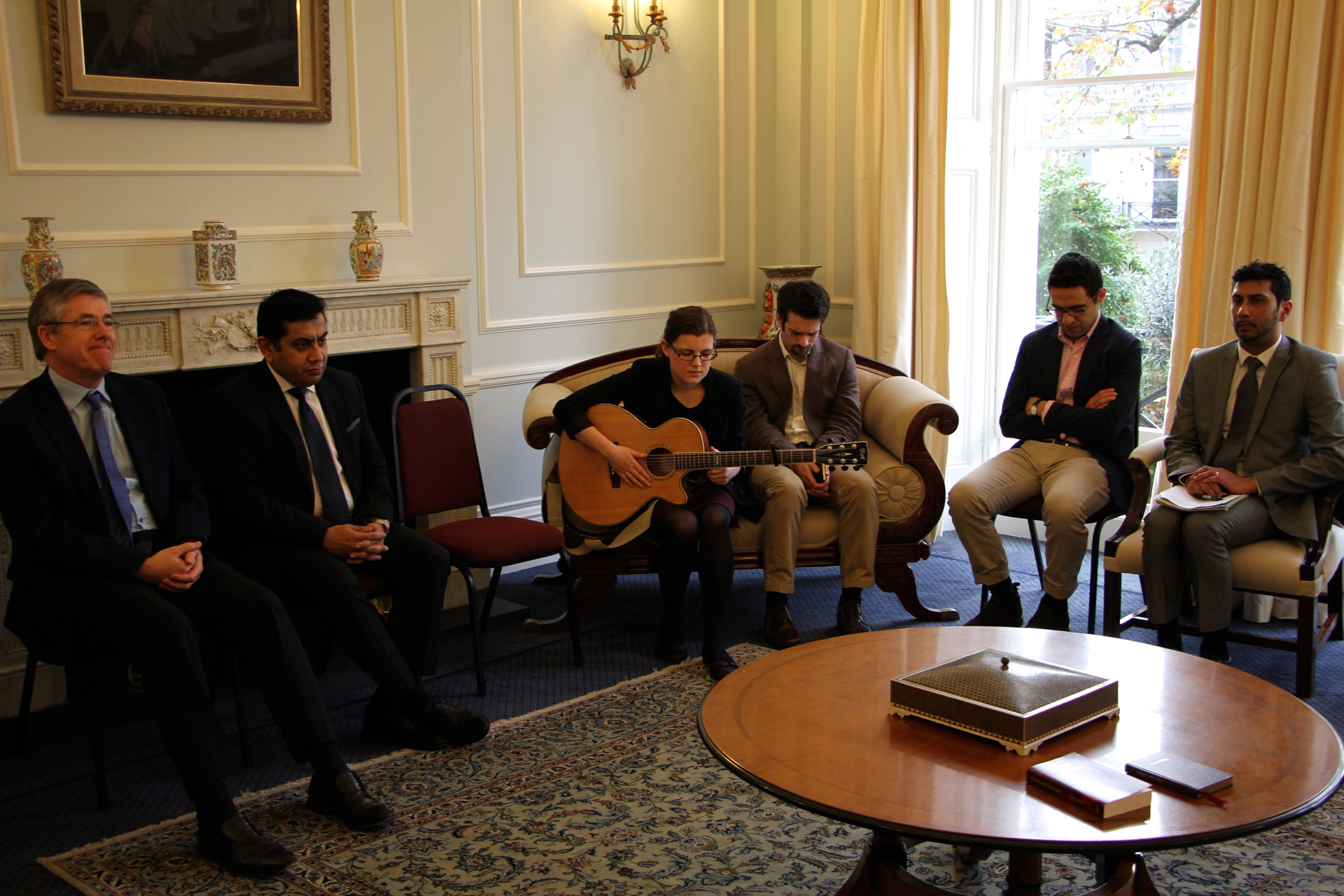 Members of the Bahai community and Lord Ahmad sit together during the programme, which included prayers and music